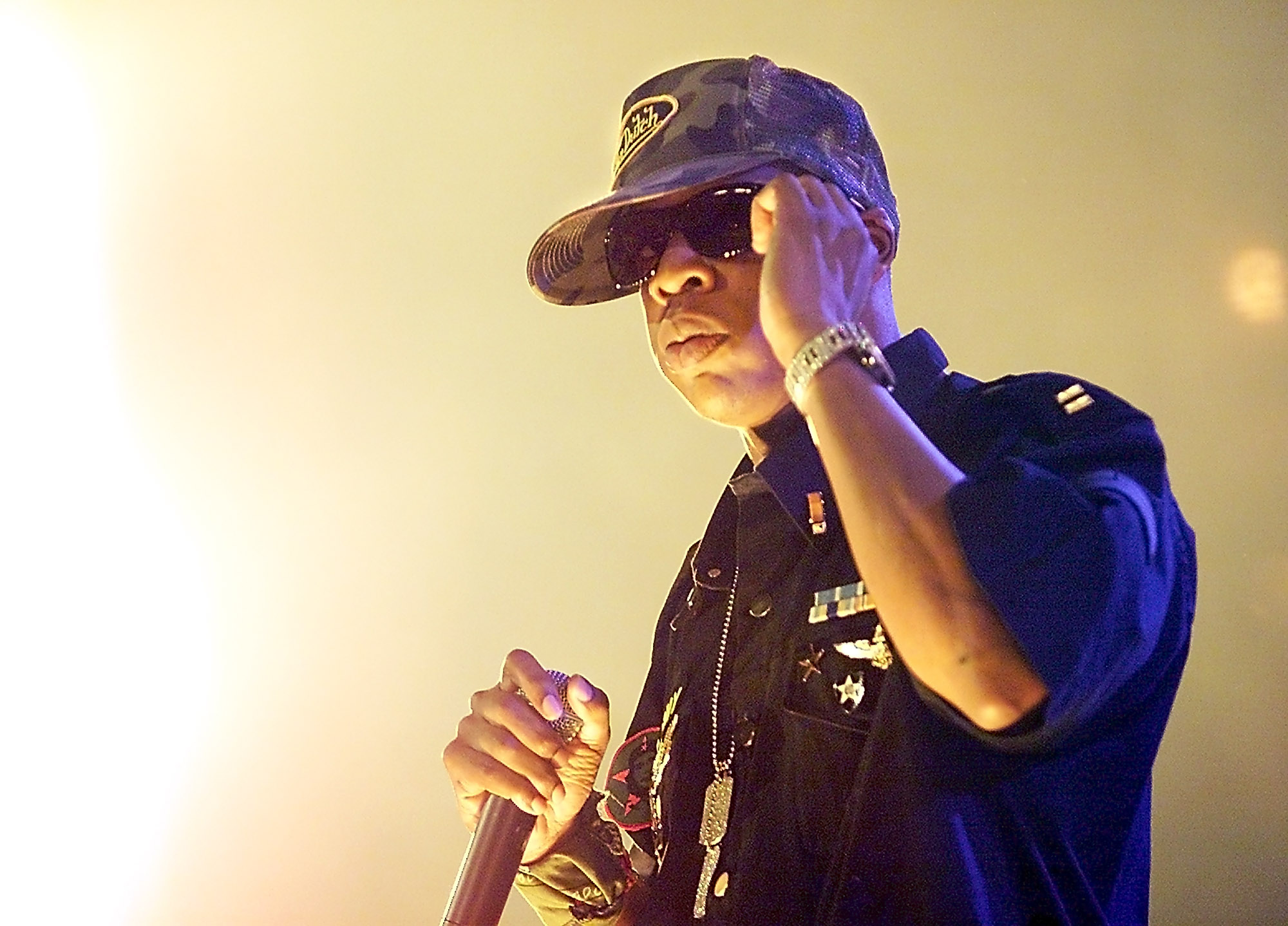 Rapper Jay-Z adjusts his sunglasses as he performs during a stop on the Roc the Mic tour at the Mark of the Quad-Cities in Moline, Ill., Tuesday, July 15, 2003